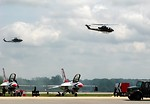Free Stock Photo: AH-1F Cobra attack helicopters flying in the sky over a runway with Thunderbird jets
