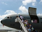 Free Stock Photo: Front view of a military plane on the runway with people on truck mounted passenger stairs