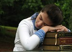 Free Stock Photo: A young schoolgirl resting her head on a stack of books