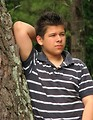 Free Stock Photo: A young latino man posing outdoors by a tree