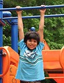 Free Stock Photo: A young latino boy hanging from bars on a playground