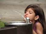 Free Stock Photo: A cute young latina girl drinking from a water fountain