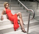 Free Stock Photo: A beautiful woman in a red dress posing on stairs.