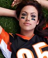 Free Stock Photo: A beautiful woman in a football jersey lying in the grass.