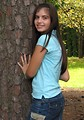 Free Stock Photo: A beautiful latina teen girl posing against a tree