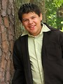 Free Stock Photo: A teen latino boy posing outdoors by a tree