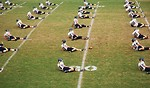 Free Stock Photo: High school football players doin warm up exercises on a field