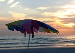 Free Stock Photo: A beach umbrella in front of a sunset